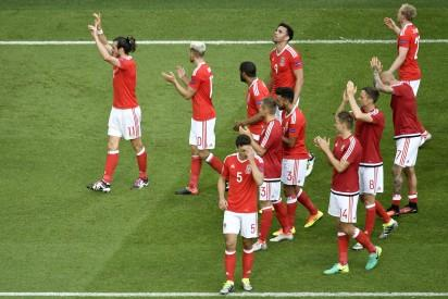 Wales' forward Gareth Bale  (L) and Wales' midfielder Aaron Ramsey clap as the team celebrates its 1-0 win in the Euro 2016 round of sixteen football match Wales vs Northern Ireland, on June 25, 2016 at the Parc des Princes stadium in Paris. / AFP PHOTO / PHILIPPE LOPEZ