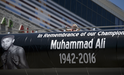 A woman walks on a pedestrian bridge from the Muhammad Ali Center June 9, 2016 in Louisville, Kentucky. Two days of funeral ceremonies bidding farewell to Muhammad Ali got underway Thursday with a Muslim prayer service in the Kentucky hometown of the beloved boxing legend and civil rights hero. / AFP PHOTO
