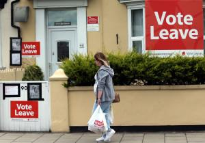 "A woman walks past a house where ""Vote Leave"" boards are displayed in Redcar, north east England on June 27, 2016 Britain's historic decision to leave the 28-nation bloc has sent shockwaves through the political and economic fabric of the nation. It has also fuelled fears of a break-up of the United Kingdom with Scotland eyeing a new independence poll, and created turmoil in the opposition Labour party where leader Jeremy Corbyn is battling an all-out revolt.  / AFP PHOTO"