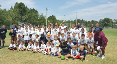 Kids that attended the summer soccer camp at USC with the coaches. Standing right is Ofoje.