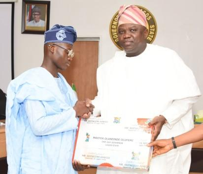 Lagos State Governor, Mr. Akinwunmi Ambode (right), presenting a gift to the Winner of 2016 Spelling Bee Competition and One-Day Governor, Master Olaseinde Olufemi of Shasha Community Senior High School (left) during the 2016 One-Day Governor's visit, at the Exco Chambers, Lagos House, Ikeja, on Friday, July 08, 2016.(File)