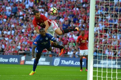 Manchester United's Swedish striker Zlatan Ibrahimovic (up) beats Leicester City's English defender Wes Morgan (down) to head in their second goal during the FA Community Shield football match between Manchester United and Leicester City at Wembley Stadium in London on August 7, 2016. / AFP PHOTO / GLYN KIRK /