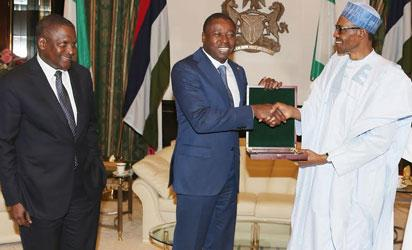R-L;  President Muhammadu Buhari present a gift to the Togolese President, Mr Faure Gnassingbe with him is President Dangote Group of Company, Alhaji Aliko Dangote during a courtesy visit at the State House in Abuja