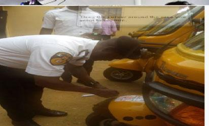 Chief Vehicle Inspection Officer, CVIO, in the state, Engr Paul Bepeh pasting a road-worthiness tag on a tricycle.