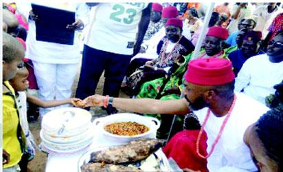 Chidoka giving out pieces of yams to a child