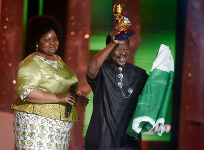 Nigerian music legend King Sunny Ade, holding national green and white flag, raises his award after receiving the award from African Union Commission head of culture, Angela Martins (L) during the All Africa Music Awards (AFRIMA) ceremony in Lagos on November 6, 2016. The All Africa Music Awards is designed to recognise and reward artists who have given African music the most creative competitive edge in the global market within the year under review. AFP