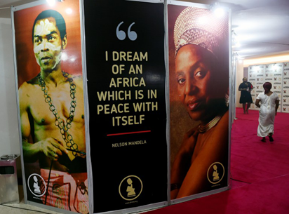 Guests walk past banners with photographs of Nigerian afrobeat music legend Fela Anikulapo Kuti (L) and South African Miriam Makeba during the All Africa Music Awards (AFRIMA) ceremony in Lagos on November 6, 2016. The All Africa Music Awards is designed to recognise and reward artists who have given African music the most creative competitive edge in the global market within the year under review. AFP