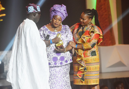 Widow (C), flanked by daughter (R) of the late iconic musician from the Democratic Republic of Congo, Papa Wemba, receives a posthumous award in honour of her husband during the All Africa Music Awards (AFRIMA) ceremony in Lagos on November 6, 2016. The All Africa Music Awards is designed to recognise and reward artists who have given African music the most creative competitive edge in the global market within the year under review. AFP