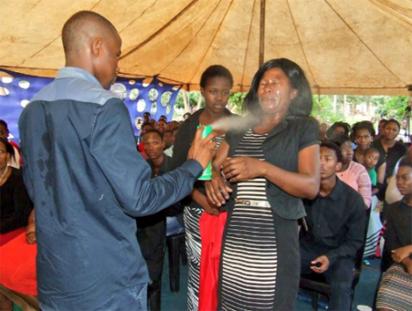 Pastor Lethebo Rabalago spraying insect killer on a member