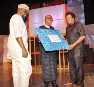 "Minister of Information and Culture Lai Mohammed (Middle) receiving a souvenir from Makin Soyinka during the Command Performance of ''Death and the King's Horseman"" in Lagos on Saturday to commemorate the 30th anniversary of the award of Nobel Prize to Prof. Wole Soyinka.   Artistic Director of the National Troue Akin Adejuwon (Left) looks on"