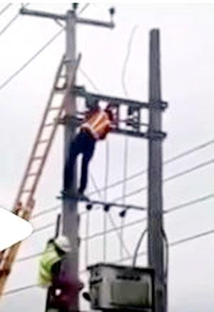 The victim's colleagues (top and bottom) bringing down the body (not shown) from the electric pole, at the scene of the incident, yesterday.