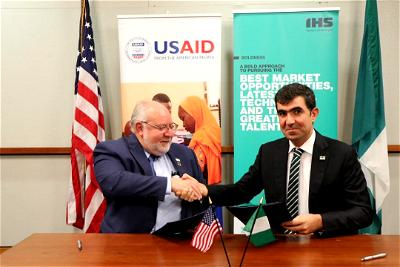 USAID Mission Director, Stephen M. Haykin; IHS Nigeria CEO, Mohamad Darwish at a signing event to announce IHS Nigeria's support for USAID's HIV/AIDS Eradication Efforts in commemoration of World AIDS Day.